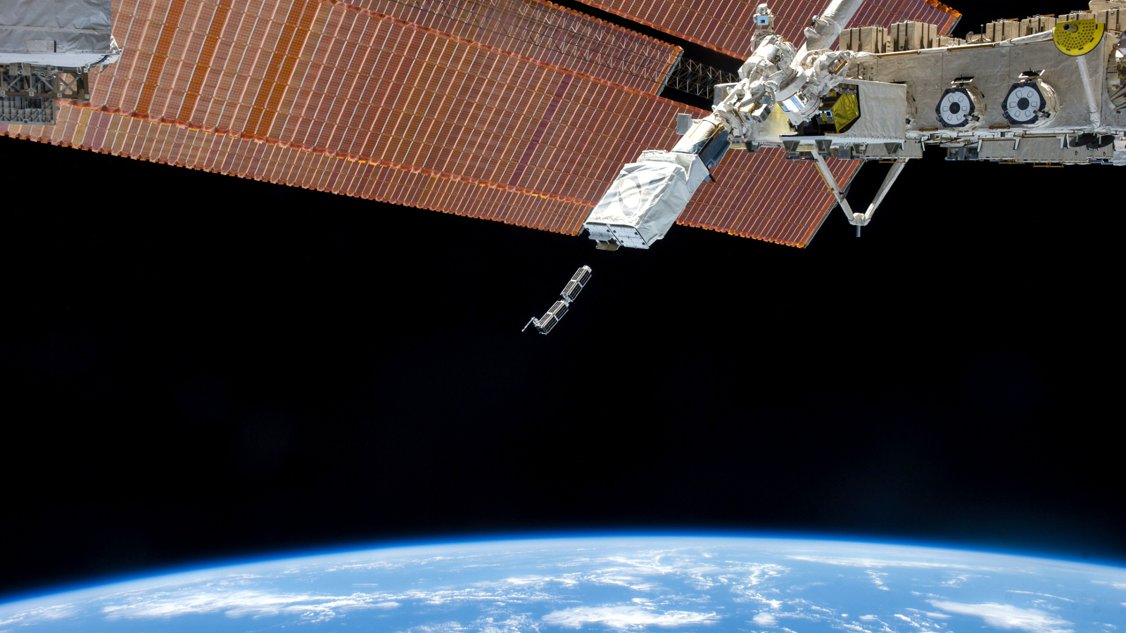 The Small Satellite Orbital Deployer (SSOD), in the grasp of the Kibo laboratory robotic arm, is photographed by an Expedition 38 crew member on the International Space Station as it deploys a set of NanoRacks CubeSats in this February 11, 2014 NASA photo. The CubeSats program contains a variety of experiments such as Earth observations and advanced electronics testing. Station solar array panels, Earth's horizon and the blackness of space provide the backdrop for the scene.