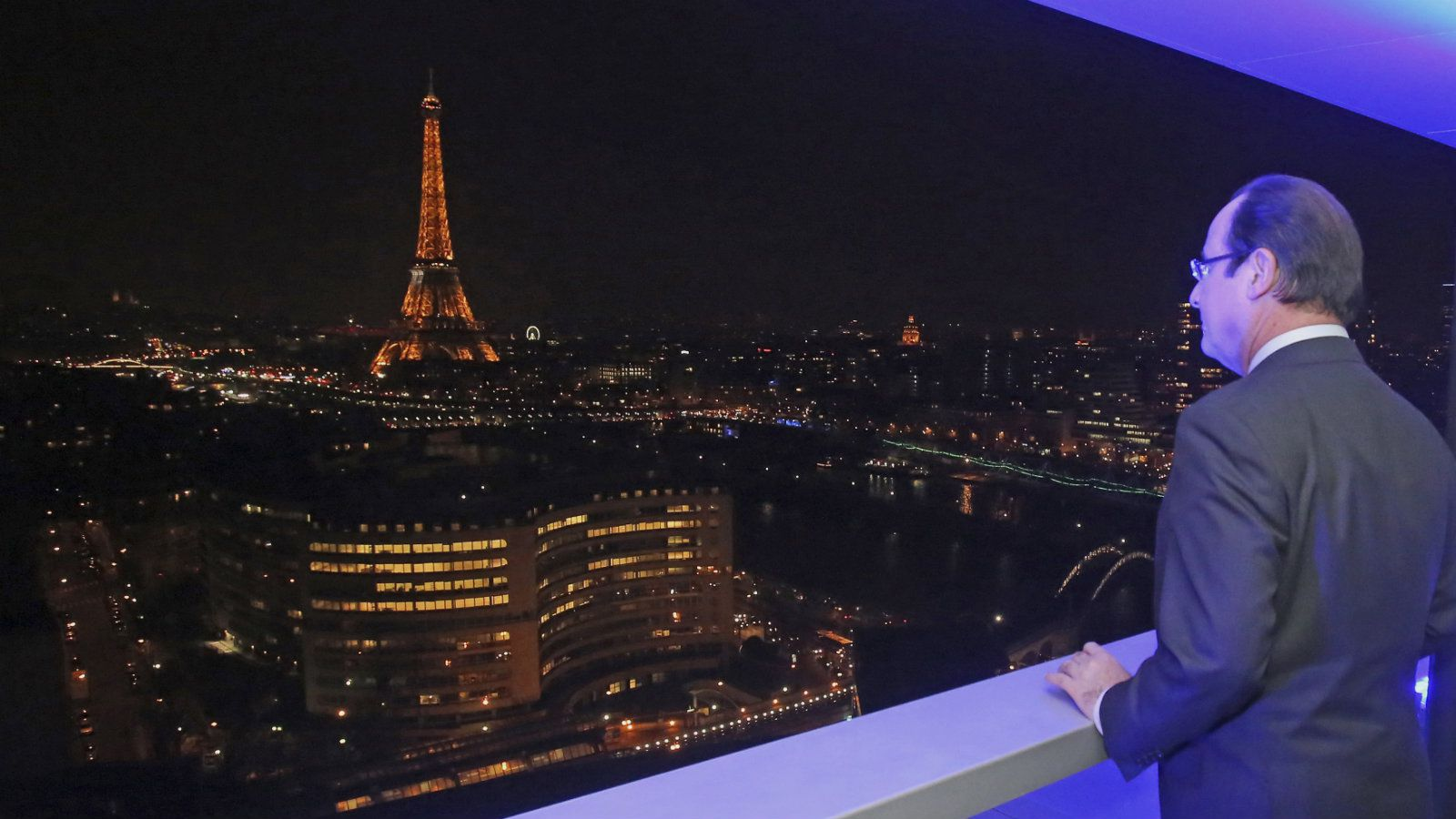 French President Francois Hollande looks at the Paris skyline, including the Eiffel Tower, at night as he visits the Radio France headquarters at the occasion of the 5Oth anniversary of the creation of Radio France, in Paris, December 17, 2013. REUTERS/Remy de la Mauviniere/Pool (FRANCE - Tags: POLITICS MEDIA)