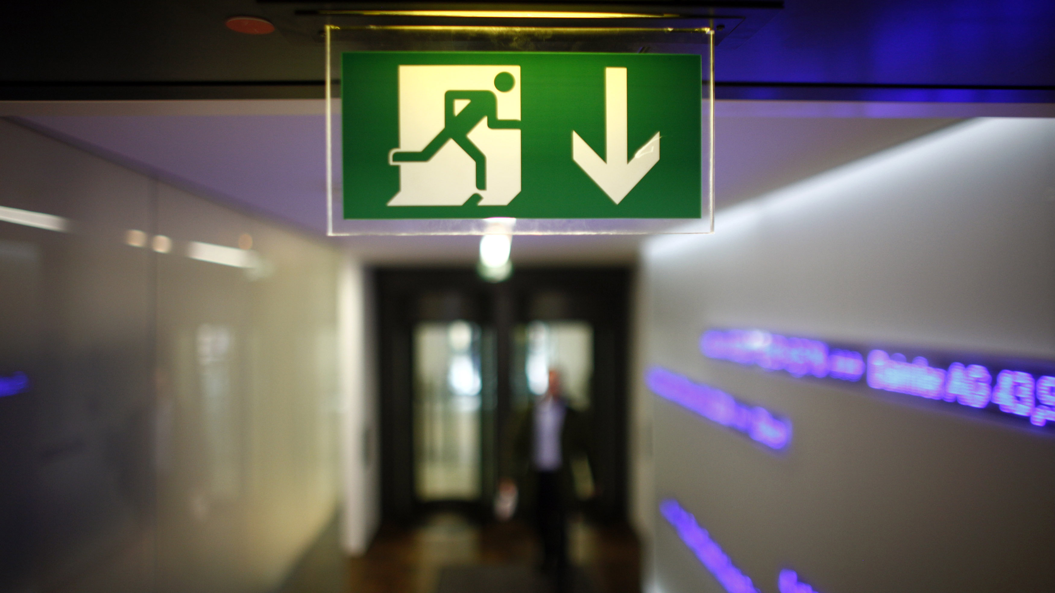 A bourse trader enters the trading floor under a emergency exit sign at Frankfurt's stock exchange, September 14, 2010.