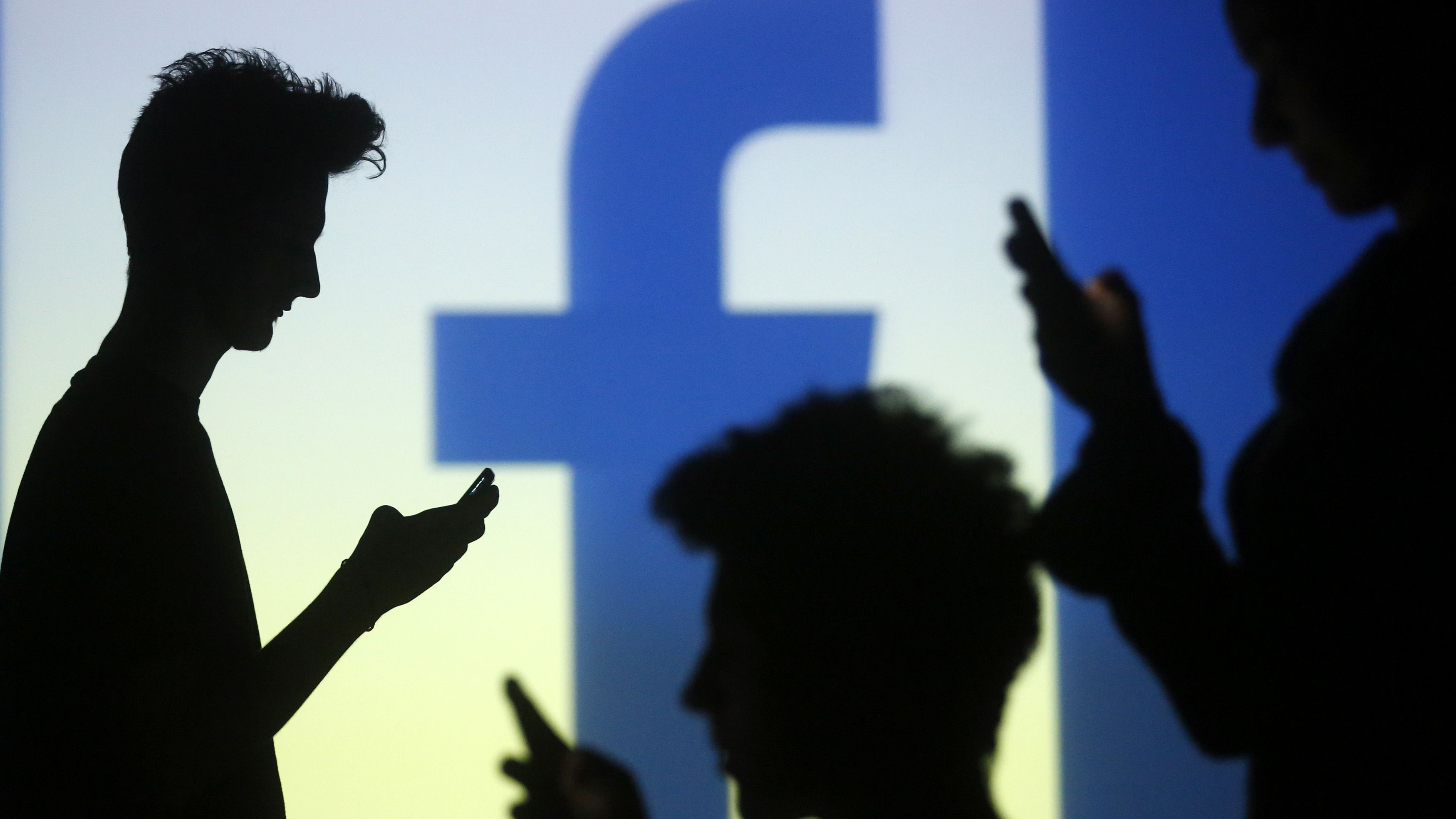 People are silhouetted as they pose with mobile devices in front of a screen projected with a Facebook logo, in this picture illustration taken in Zenica October 29, 2014. Facebook Inc warned on Tuesday of a dramatic increase in spending in 2015 and projected a slowdown in revenue growth this quarter, slicing a tenth off its market value. Facebook shares fell 7.7 percent in premarket trading the day after the social network announced an increase in spending in 2015 and projected a slowdown in revenue growth this quarter. REUTERS/Dado Ruvic (BOSNIA AND HERZEGOVINA - Tags: BUSINESS SCIENCE TECHNOLOGY BUSINESS LOGO) - RTR4C0VB