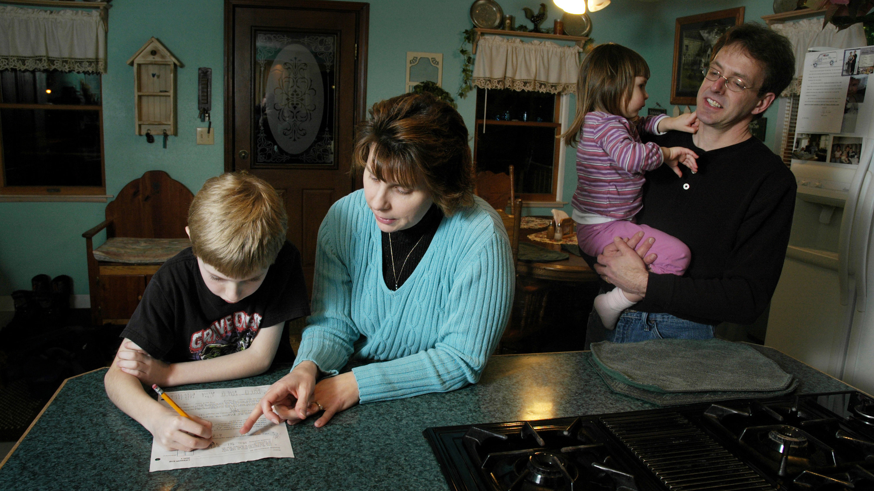 Grace Case, second left, helps her son Adam, left, with his math homework as her husband, Dan, right, and daughter Emily look on at their home in Fulton, N.Y., Thursday, Jan. 29, 2009. The Cases, who accumulated over $40,000 in credit card debt, now live a frugal lifestyle in an effort to pay down the debt.