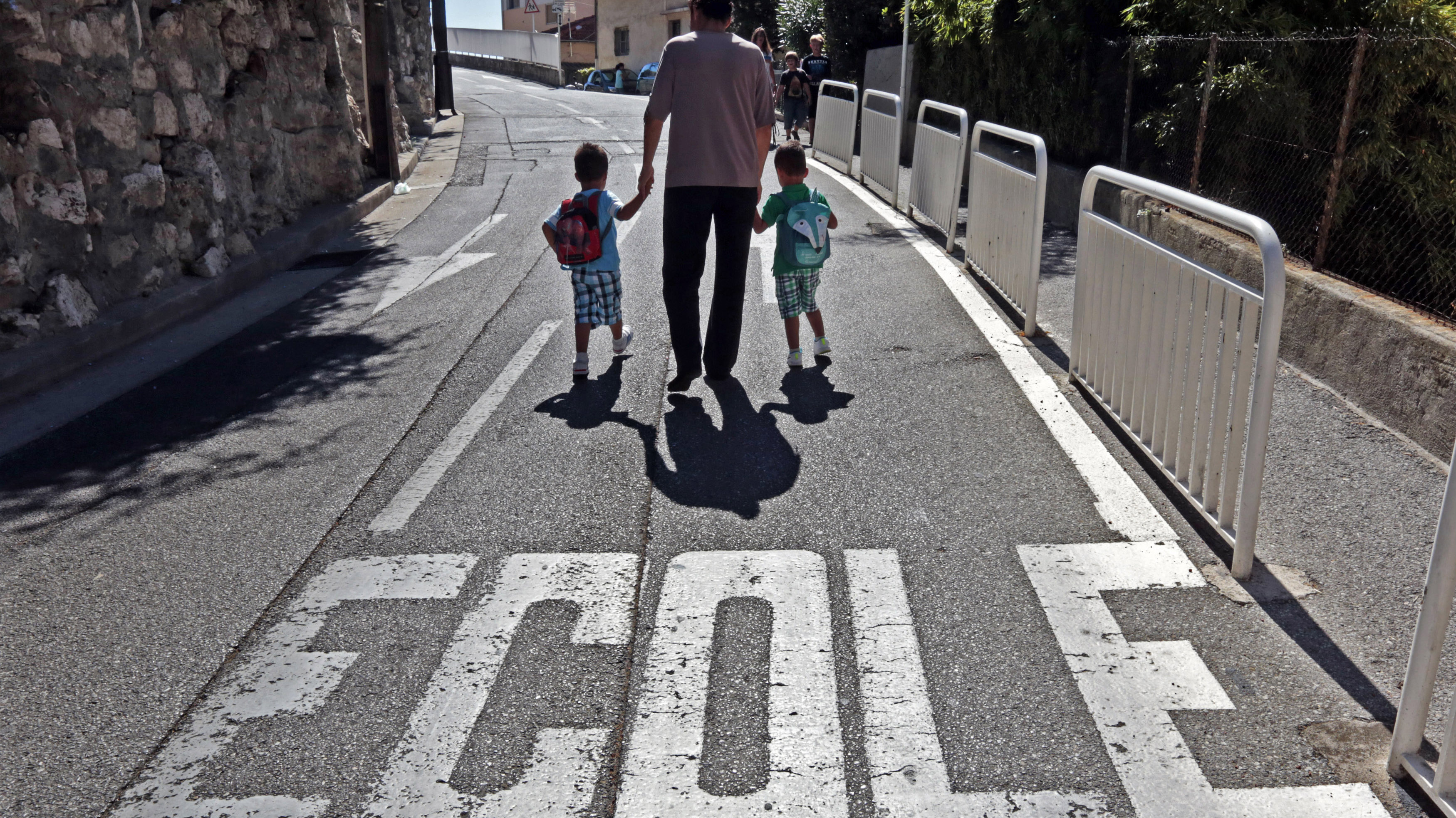"A mother walks on the street with her children near a road marker which reads ""Ecole"" (school) on the first day of class in the new school year in Nice, September 3, 2013."