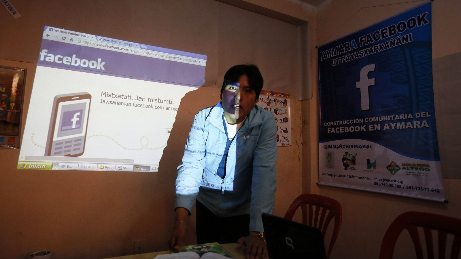 """Volunteer Aymara speaker Elias Quispe and head of online community """"Jaqi Aru"""" (language of the people) explains how to translate Facebook, in El Alto on the outskirts of La Paz May 24, 2014. Thanks to the team of volunteer translators in Bolivia, speakers of Aymara will soon have the option of seeing their mother tongue on the social media giant, Facebook. Aymara, along with Quechua and Spanish, is an official language in Bolivia and is spoken by over one million people in the Andean country. REUTERS/David Mercado (BOLIVIA - Tags: EDUCATION SCIENCE TECHNOLOGY SOCIETY)"""