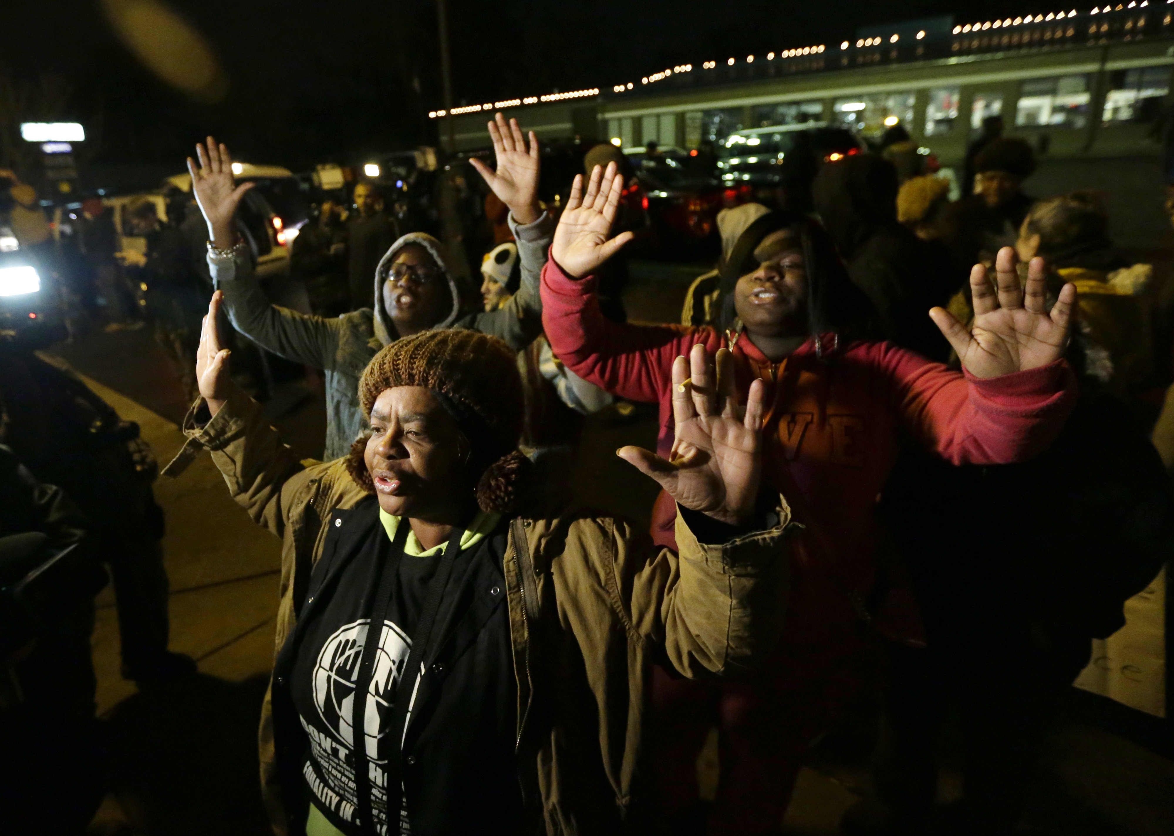 Barbara Jones, joined by other protesters, raises her hands, Monday, Nov. 24, 2014, in Ferguson, Mo., more than three months after an unarmed black 18-year-old man was shot and killed there by a white policeman.