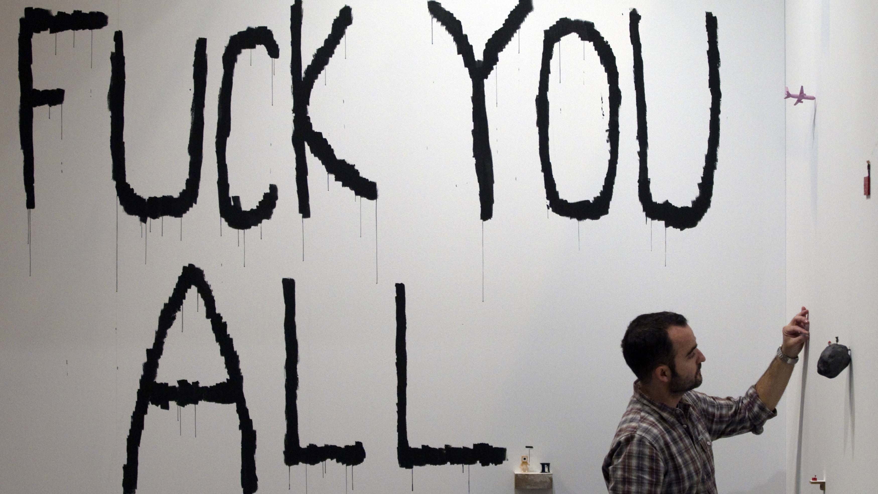 """Spanish artist Javier Calleja sets up his artwork """"Fuck You All"""" at Madrid's International Contemporary Art fair ARCO in Madrid February 15, 2011. The fair will be open from February 15 to 20."""