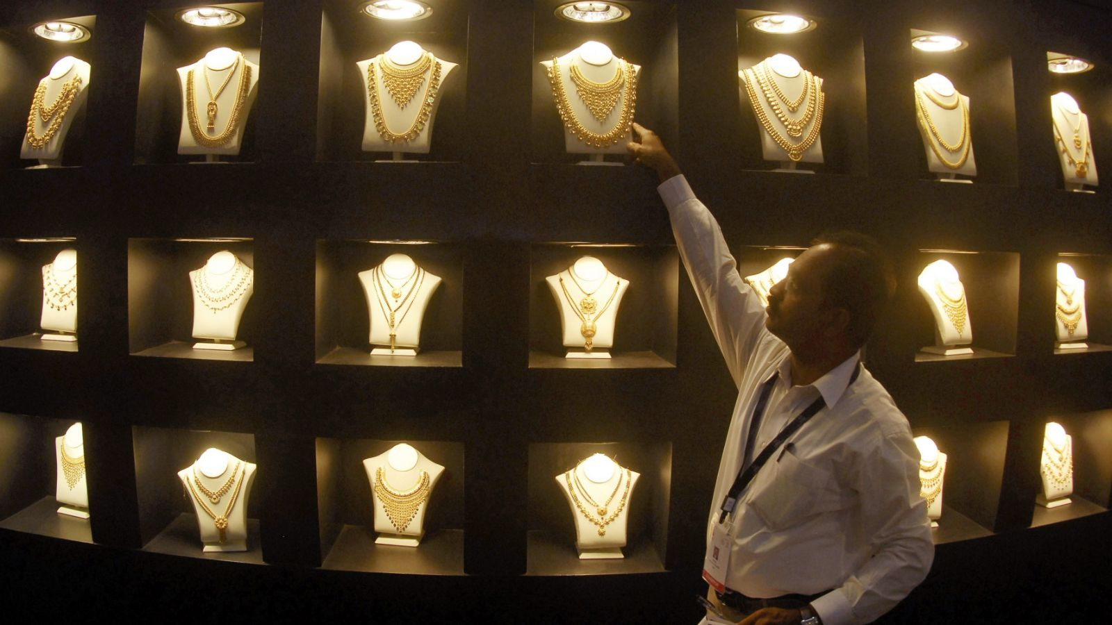 An employee displays gold necklaces at the 'Gem and Jewellery India International Exhibition 2010' (GJIIE) in the southern Indian city of Chennai January 23, 2010. India's gold traders continued to pick bargains for a third day in a row on Friday as prices remained at their 2-½ month low, but a weaker rupee weighed on sentiment, dealers said.