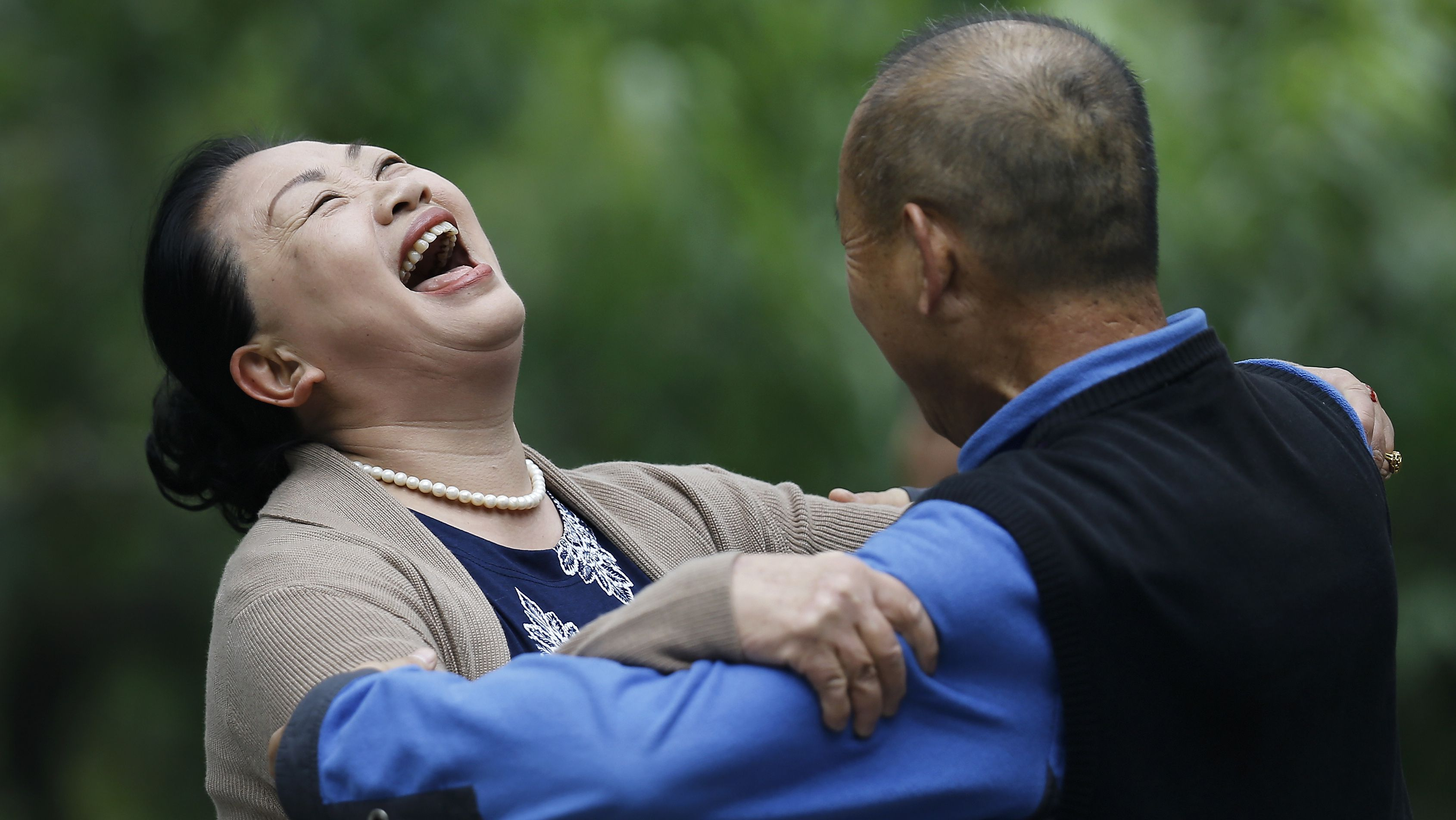 A Chinese woman laughs during a social dance with a man at Ritan Park in Beijing, China Thursday, Oct. 30, 2014. Levels of self-reported well-being in fast-growing nations like Indonesia, China and Malaysia now rival those in US, Germany and the United Kingdom, rich nations which have long topped the happiness charts, according to a Pew Research Center global survey released Friday that it showed how national income was closely linked to personal life satisfaction. (AP Photo/Andy Wong)