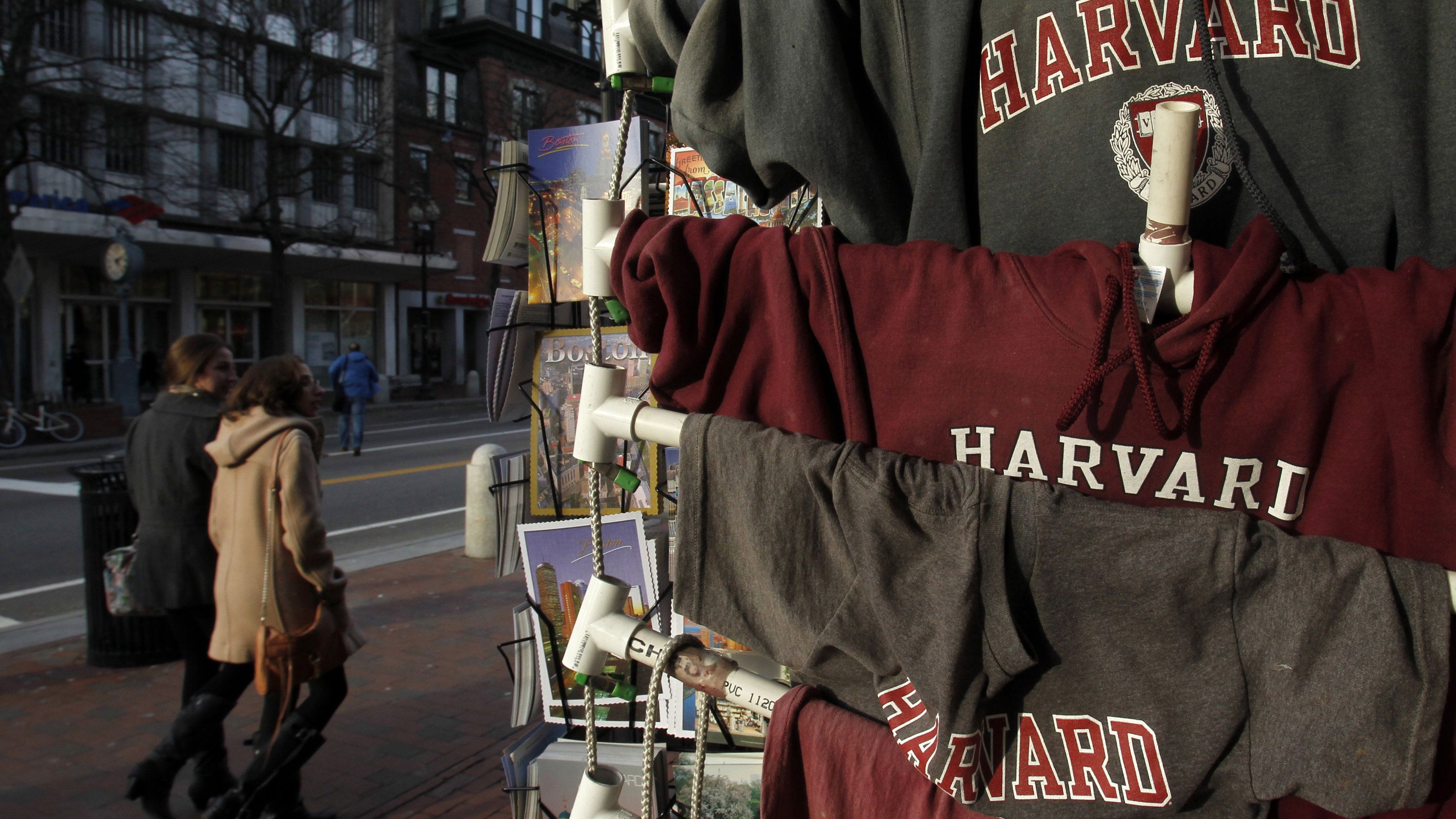People walk past Harvard University t-shirts for sale in Harvard Square in Cambridge, Massachusetts November 16, 2012.