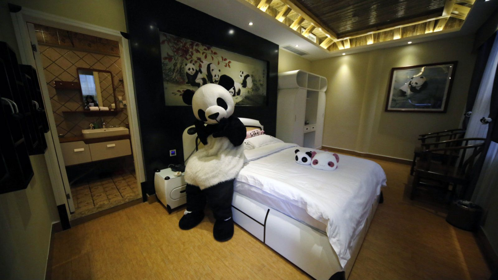 An employee dressed in a panda costume poses for a photo during the soft opening of a panda-themed hotel at the foot of Emei Mountain, Southwest China's Sichuan province, February 25, 2013. According to local media, the hotel is the first panda-themed hotel in the world and will officially open in May with room rates from 300 to 500 yuan ($48 to $80) per night. Picture taken February 25, 2013. REUTERS/China Daily (CHINA - Tags: ANIMALS SOCIETY) CHINA OUT. NO COMMERCIAL OR EDITORIAL SALES IN CHINA