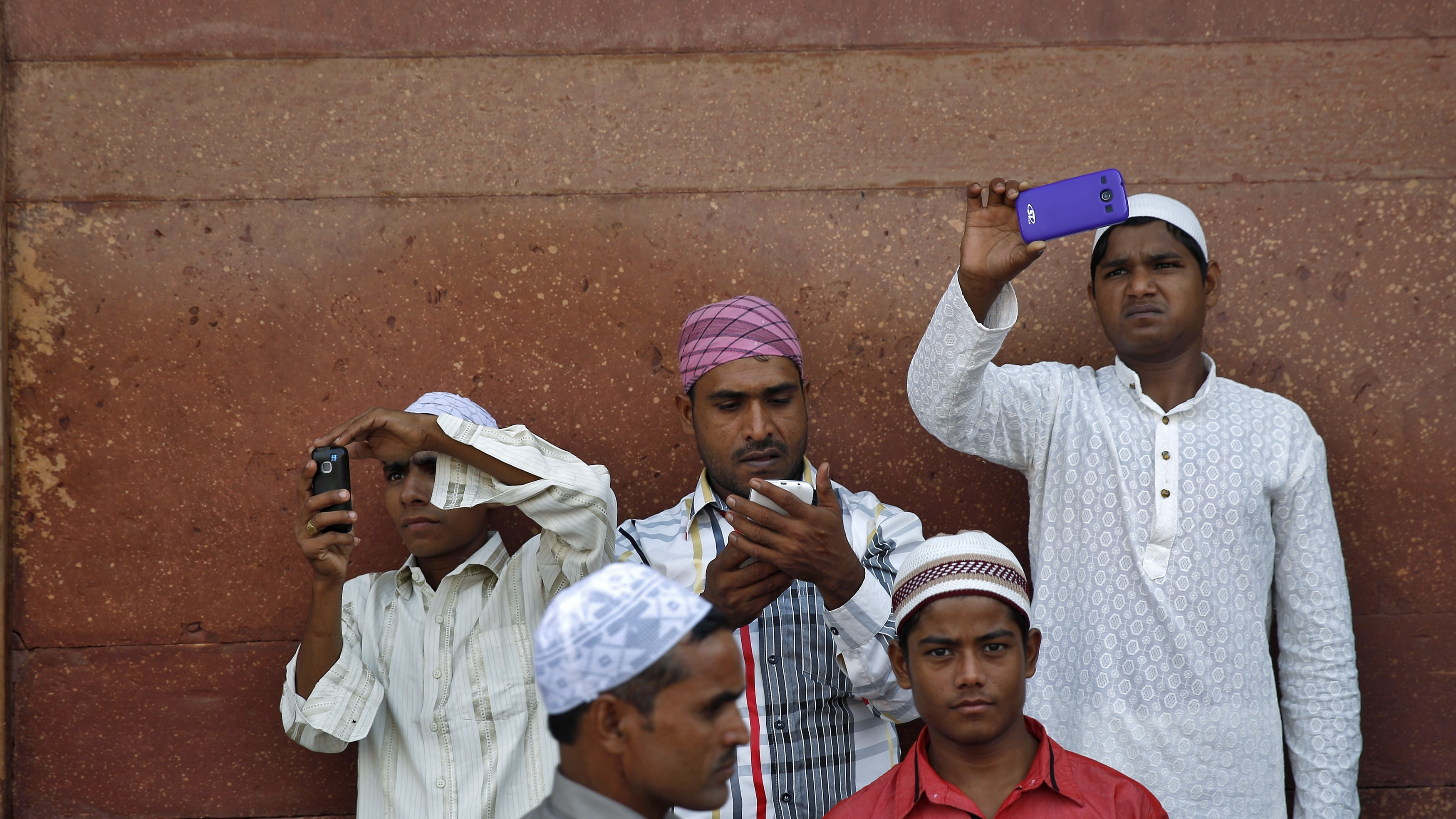 Muslims use their mobile phones after offering Eid al-Adha prayers at the Jama Masjid (Grand Mosque) in the old quarters of Delhi October 6, 2014. Muslims around the world celebrate Eid al-Adha by the sacrificial killing of sheep, goats, cows and camels to commemorate Prophet Abraham's willingness to sacrifice his son Ismail on God's command. REUTERS/Ahmad Masood