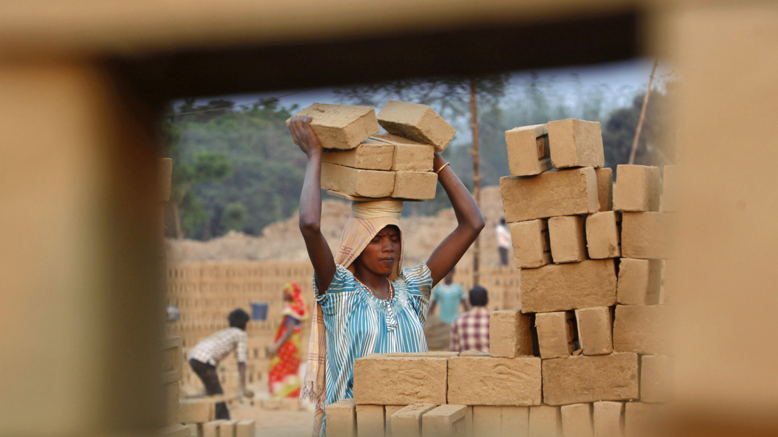 A female labourer carries bricks as she works in a brick factory on International Women's Day on the outskirts of Agartala, capital of India's northeastern state of Tripura March 8, 2013.