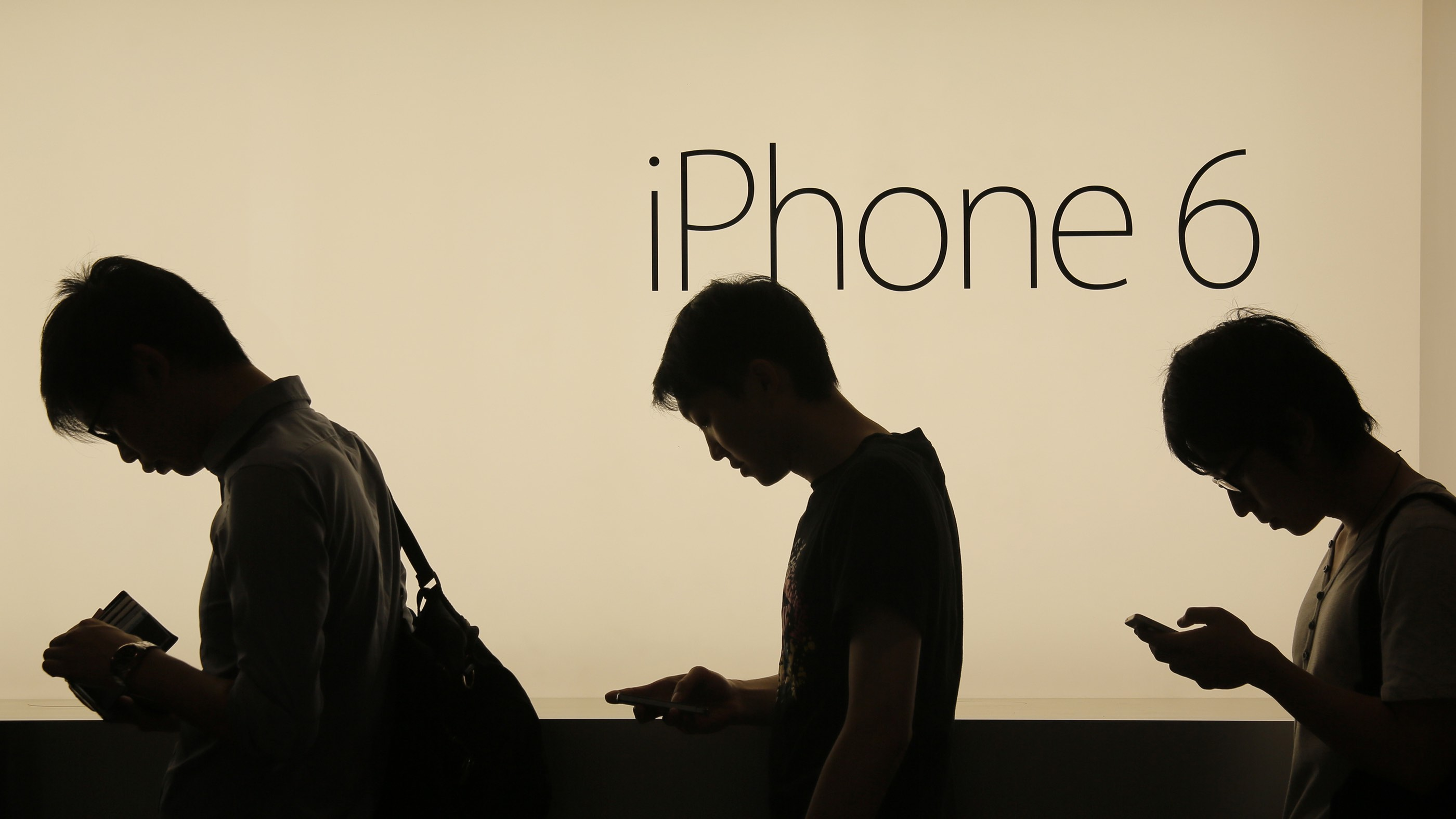 In this photo taken on Friday, Sept. 19, 2014, people wait to buy the new Apple iPhone 6 and 6 Plus devices outside an Apple store in Hong Kong. The Apple's new devices were released on Friday in Hong Kong, Singapore, Australia and Japan. (AP Photo/Vincent Yu)