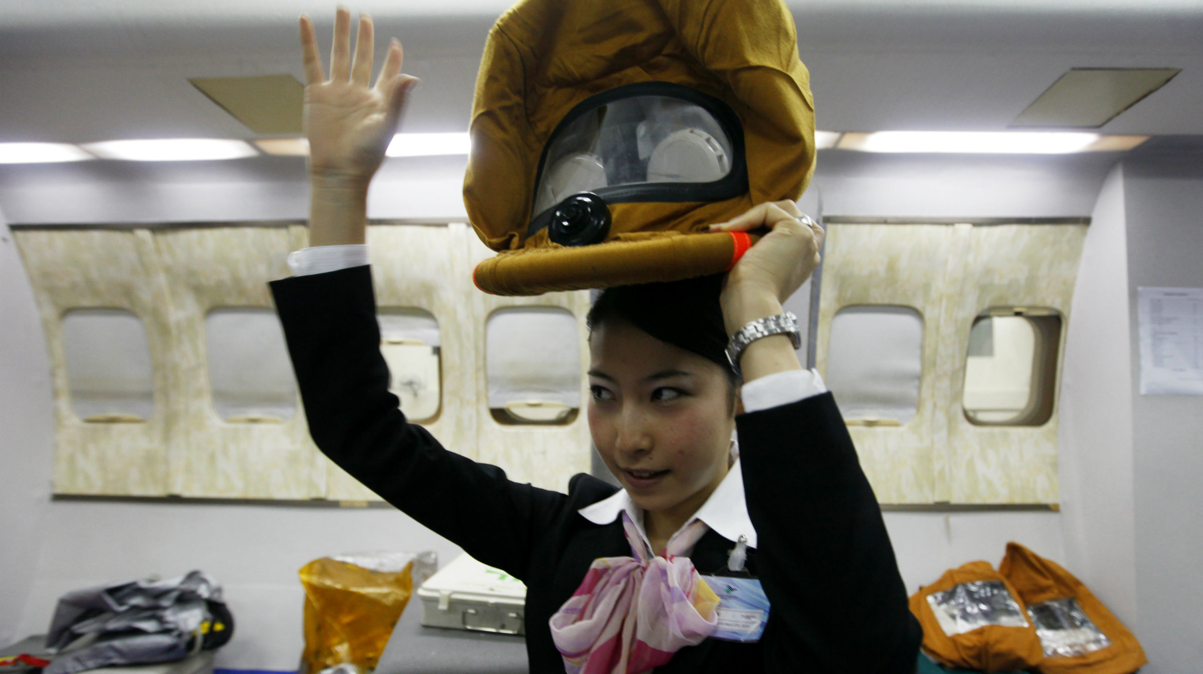 A Japanese flight attendant demonstrates head gear at a training site.