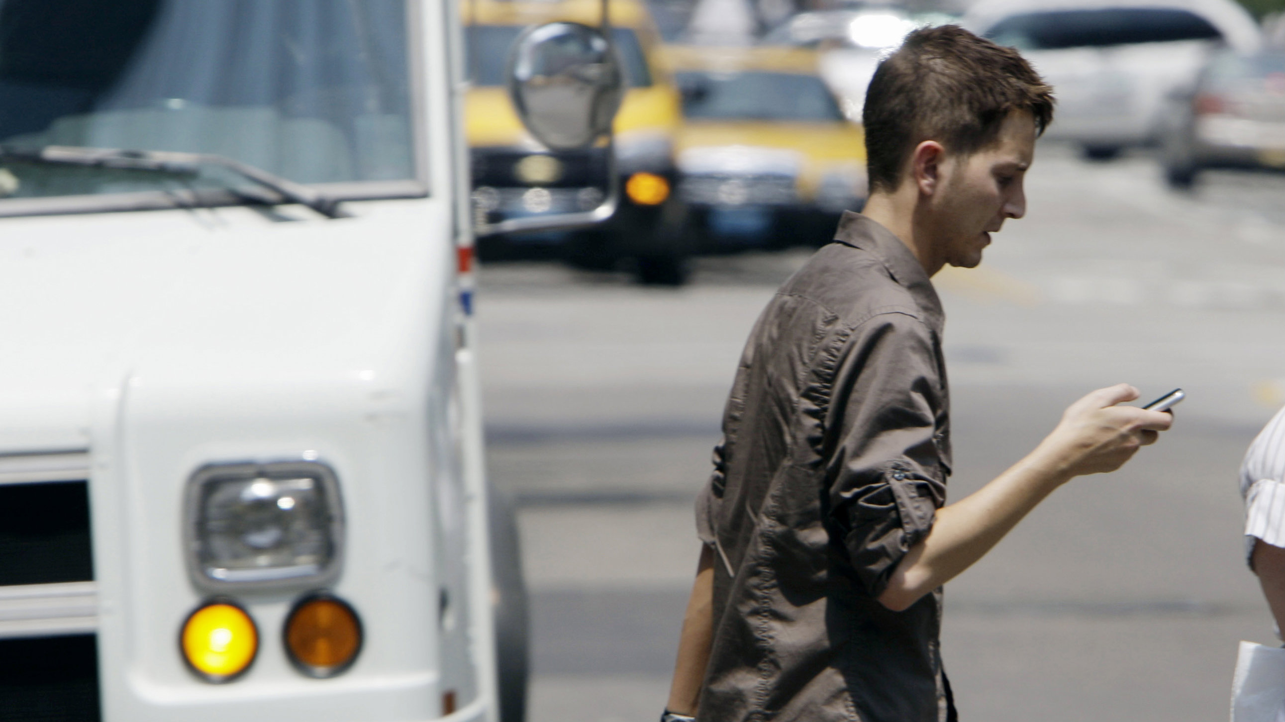 Man crossing street while texting