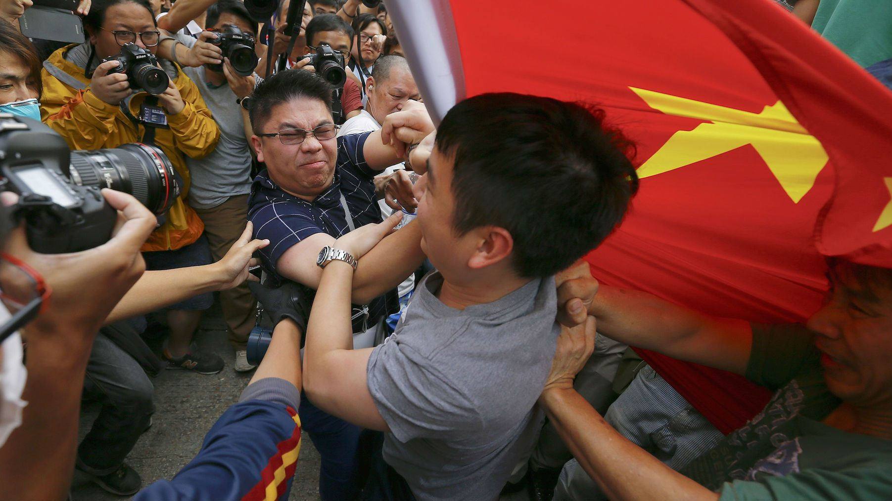 Pro-democracy demonstrators scuffle with a man (C) holding a Chinese flag who came to the protesters' barricade to oppose them blocking roads at Mongkok shopping district.