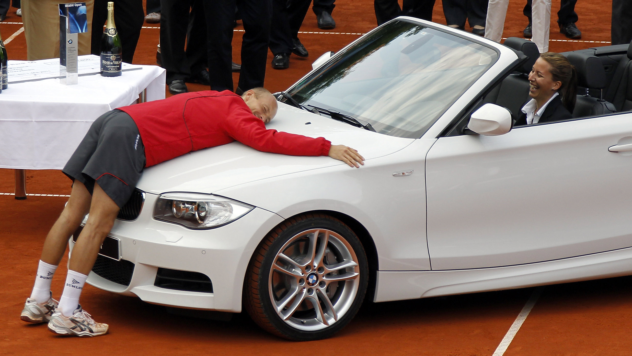 """Nikolay Davydenko from Russia reacts after winning a BMW 1 after defeating Florian Mayer from Germany in the final of ATP tennis tournament """"BMW Open"""" in Munich May 1, 2011."""