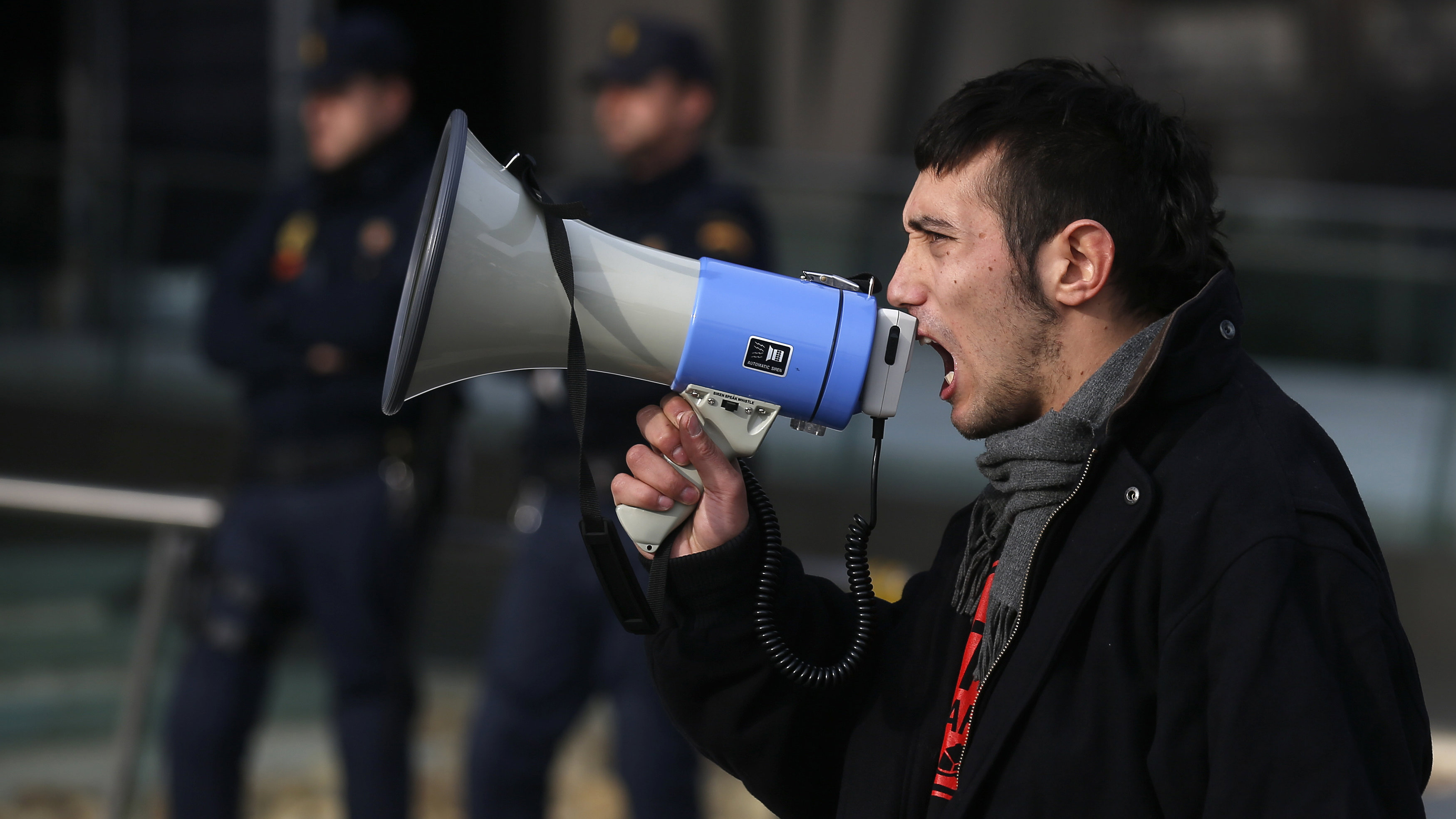 An anti-eviction demonstrator speaks into a megaphone during a protest outside Spain's Bankia bank headquarters in Madrid December 10, 2012.