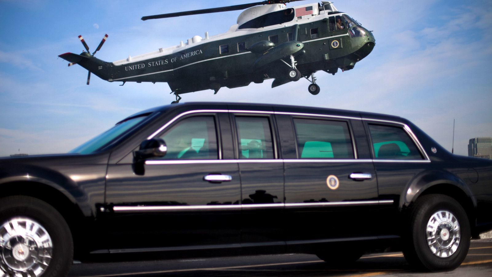 "Marine One helicopter, with President Barack Obama aboard, during landing approach at the Wall Street heliport, Tuesday, March 11, 2014 in New York. Obama traveled to New York to attend a pari of fundraisers for Democrats. Waiting to transport the President is a Secret Service agent sitting inside ""the Beast"", the armored limousine."