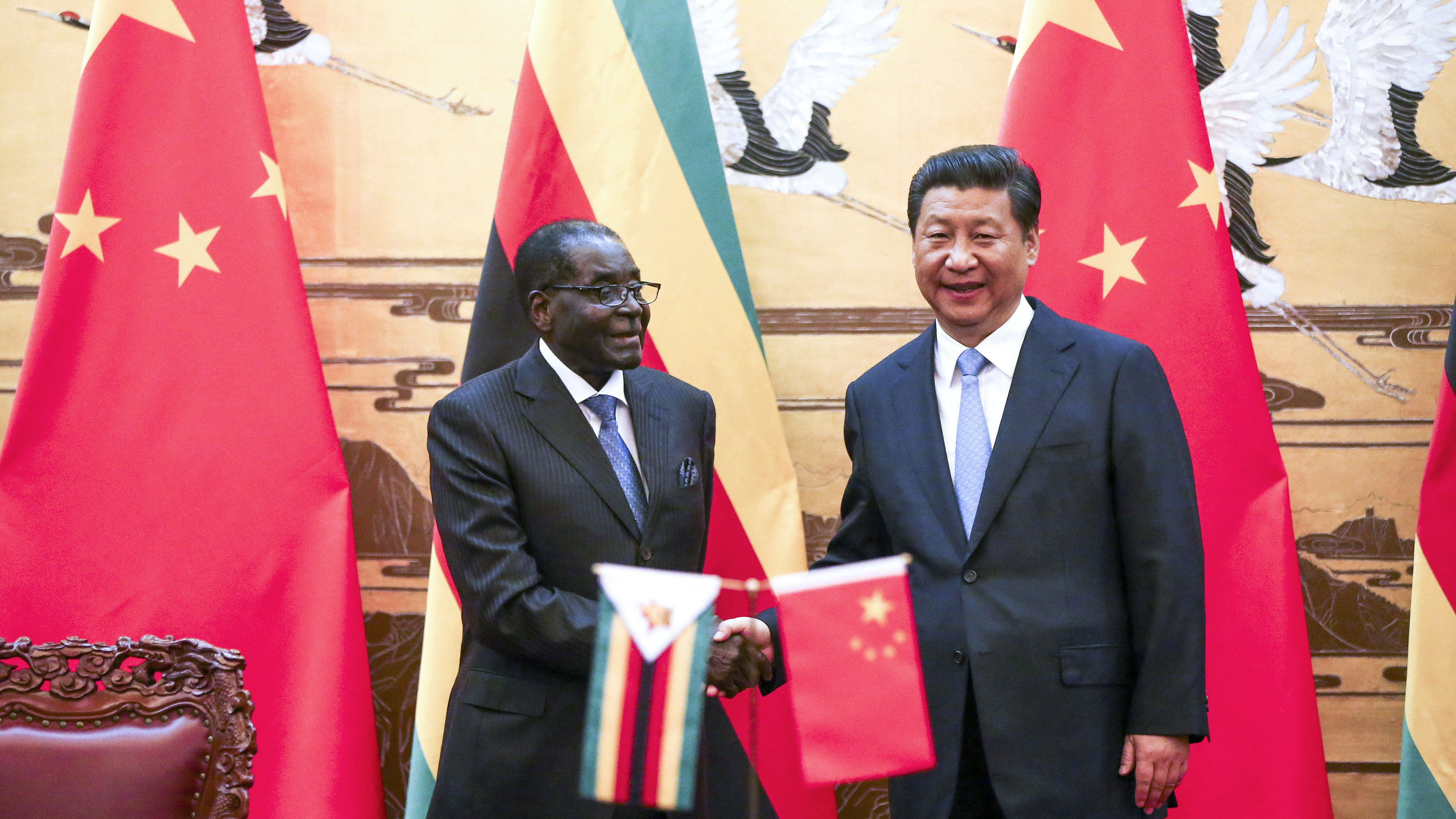 Zimbabwe's President Robert Mugabe (L) and his Chinese counterpart Xi Jinping shake hands during a signing ceremony at the Great Hall of the People in Beijing August 25, 2014.