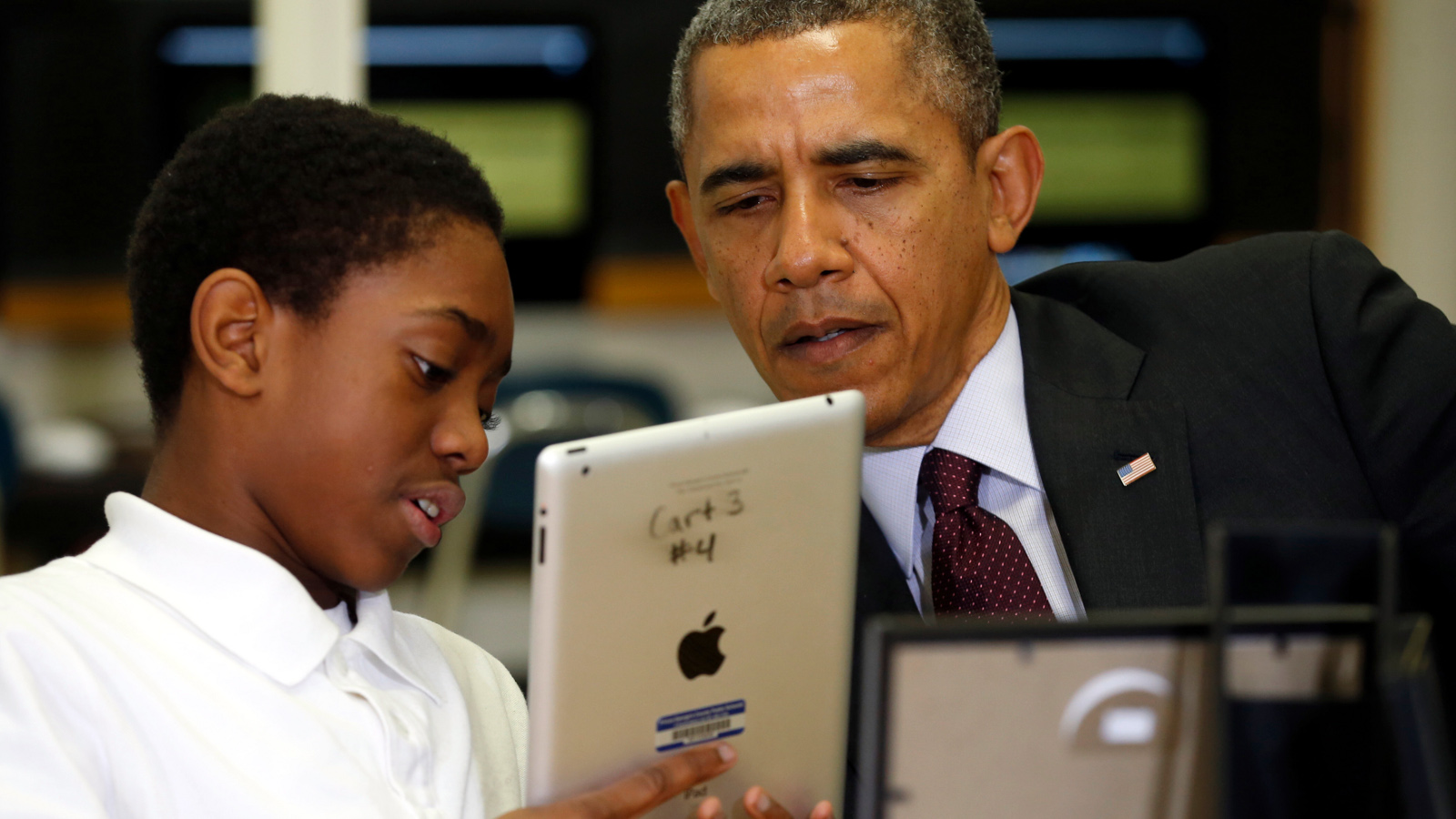 U.S. President Barack Obama talks with a student using an iPad during a visit to Buck Lodge Middle School in Adelphi, Maryland February 4, 2014. Obama made the visit to highlight the progress of his ConnectED goal of connecting 99% of students to next-generation broadband and wireless technology within five years.