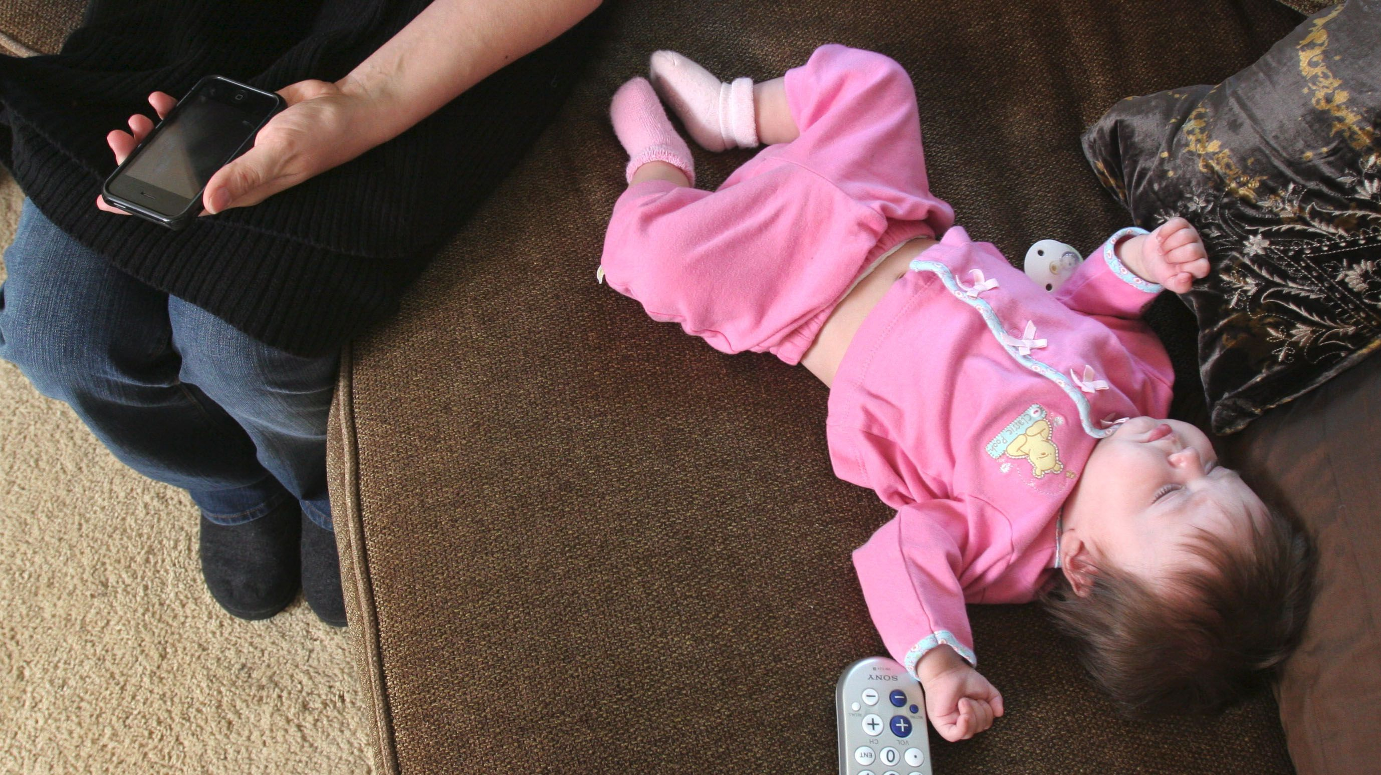 Eve Saarinen, 5 months, snoozes on the couch while her mother uses her iphone at the family's home in Shoreview, Minn., on Saturday, May 17, 2009. (AP PHOTO/ THOMAS WHISENAND)