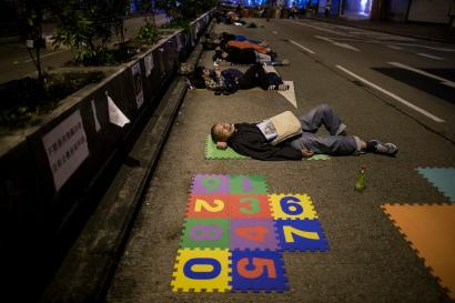 Pro-democracy protesters sleep on a occupied street at Mongkok shopping district in Hong Kong