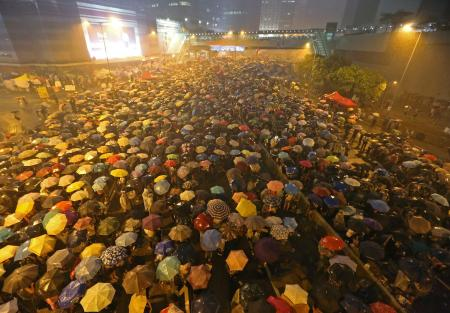 Pro-democracy protests stand in the rain near government offices in Hong Kong on Sept 30, beginning the Umbrella Movement.