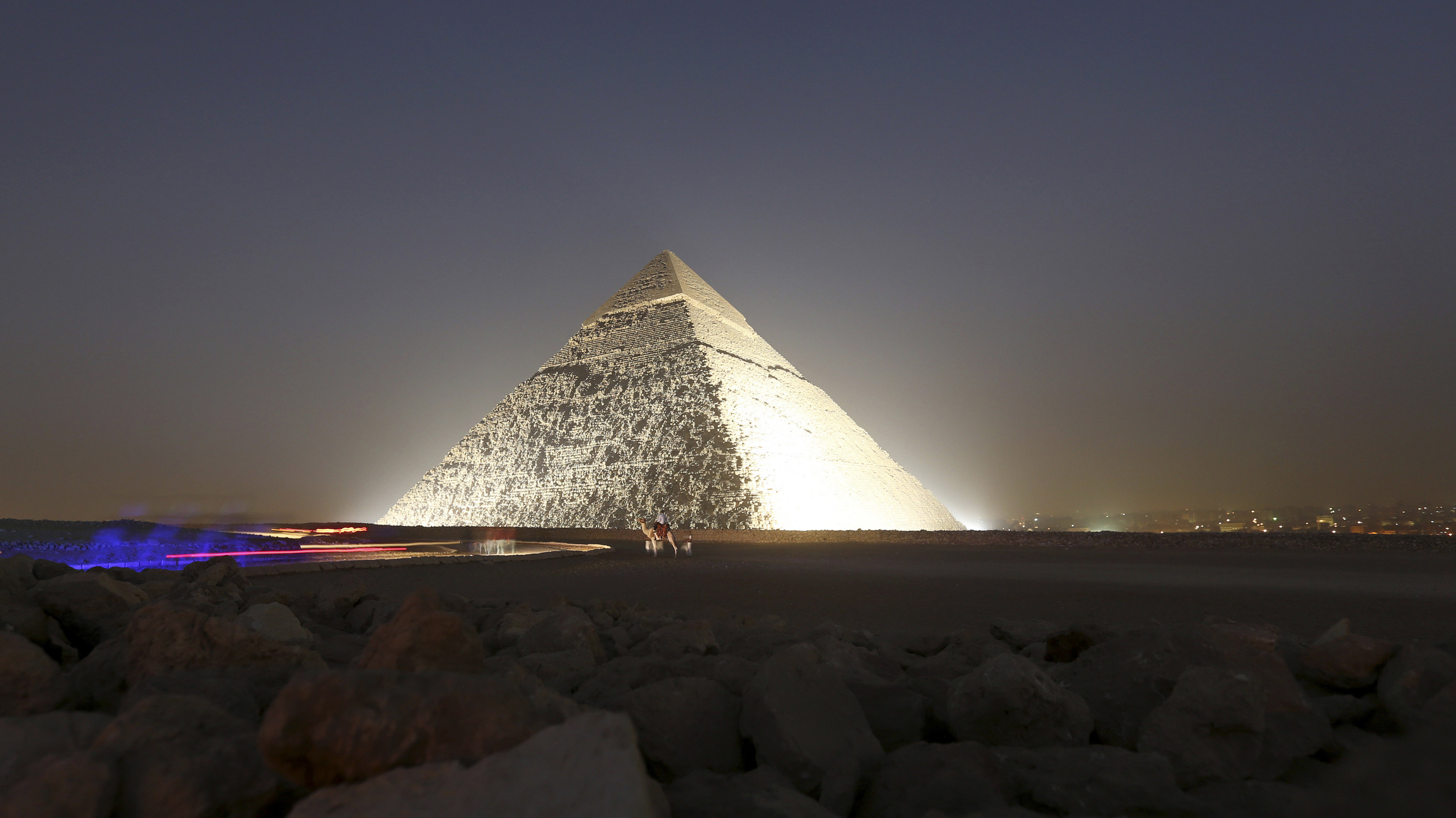 People and a camel stand next to the pyramid of Khufu, during a reopening ceremony of the Sphinx, in Giza, November 9, 2014. The Great Sphinx of Giza, which sits next to the ancient Pyramids, reopens after undergoing major restoration work, including repairs to its worn out base, in a ceremony attended by the country's top officials, including Prime Minister Ibrahim Mahlab.