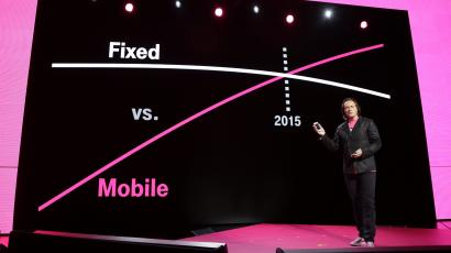 T-Mobile CEO John Legere speaks in front of a chart showing the relation of traditional fixed phone lines vs mobile phone lines at T-Mobile's Uncarrier 5.0 event, Wednesday, June 18, 2014, in Seattle. (AP Photo/Ted S. Warren)