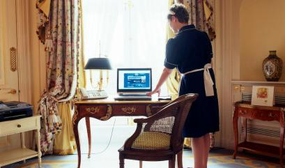 Oxanna, a chambermaid from eastern Europe, works in a bedroom at The Ritz hotel in London, April 17, 2006. When compared with a file photo from the Ritz archive taken in the 1920s the scene is much the same, with the addition of a laptop computer one of the few visible changes to the room's decor. The world famous luxury hotel will celebrate its 100th anniversary on May 24, 2006. Picture taken April 17. (Picture two of two) REUTERS/Catherine Benson - RTR1CRLR