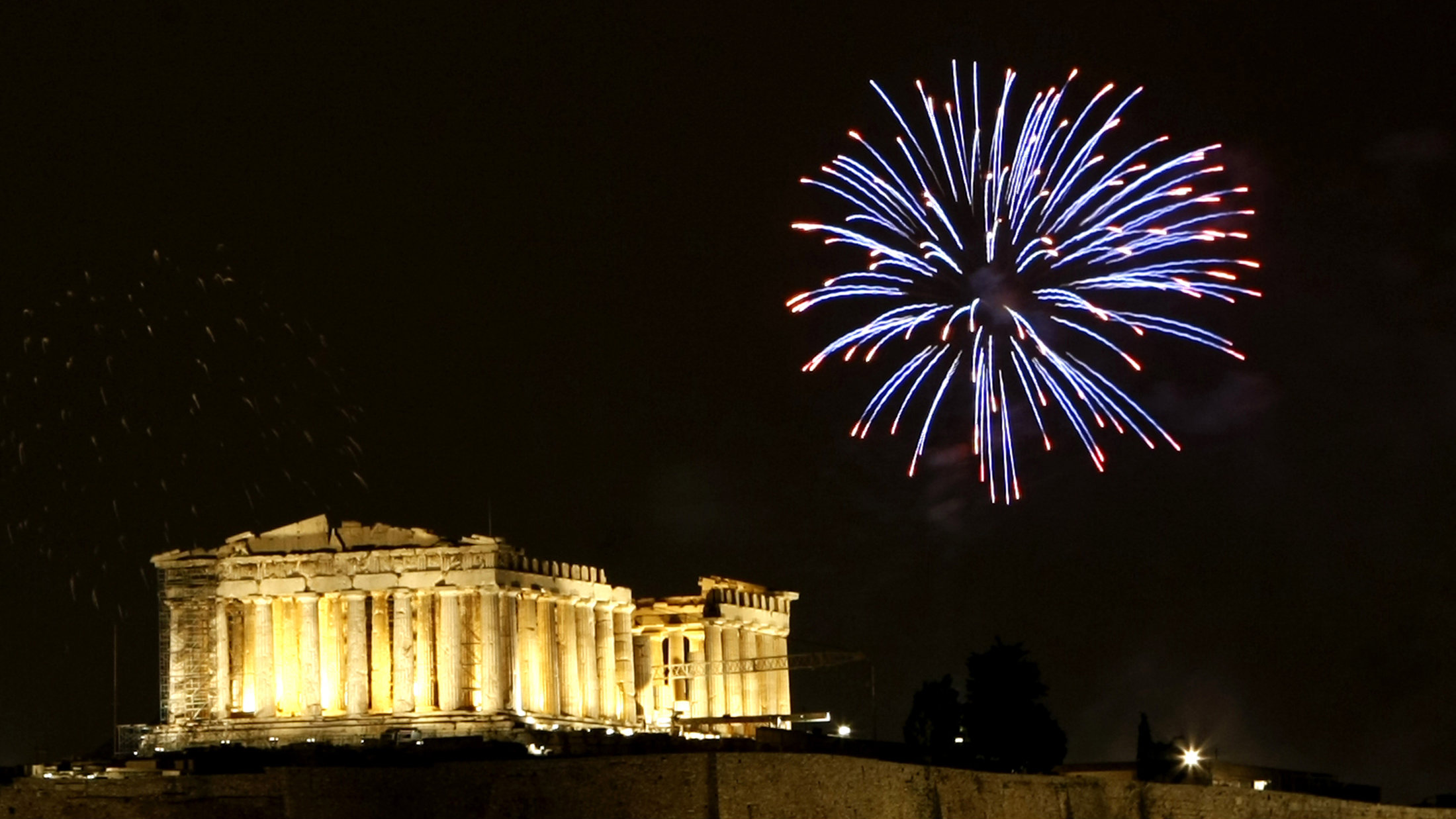 Fireworks explode over the temple of the Parthenon atop the hill of the Acropolis.