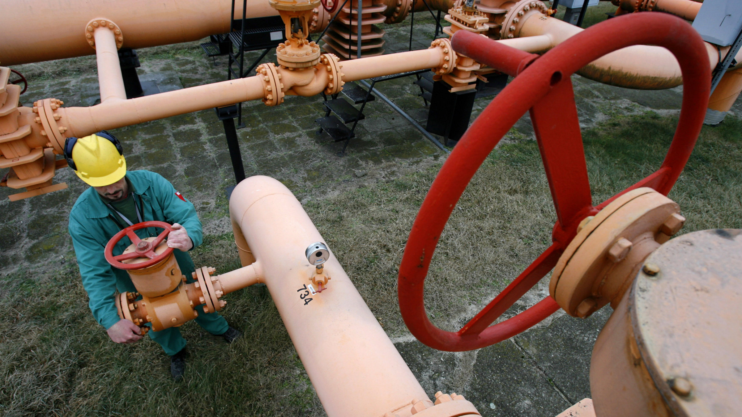 A worker controls a gas valve at a pipeline.
