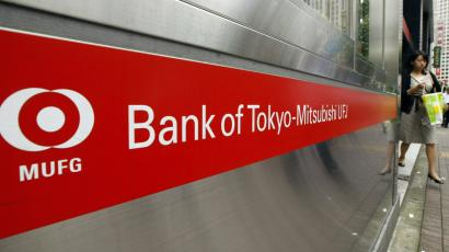 A woman comes out of a branch of Mitsubishi UFJ bank in Tokyo.