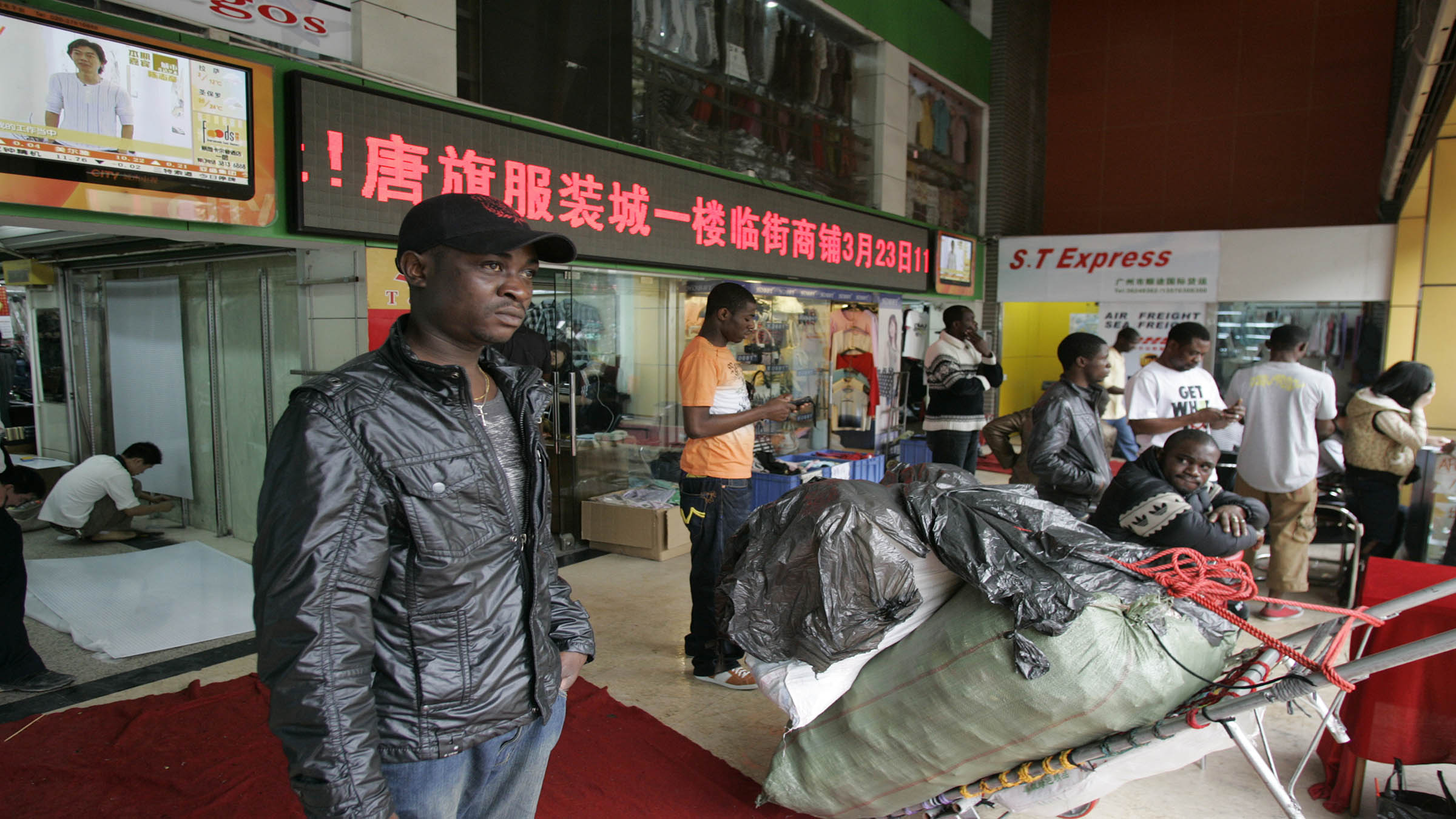 An African man stands near a shopping mall in the southern Chinese city of Guangzhou in Guangdong province March 27, 2009. In the past few years, tens of thousands of African and Arab traders have thronged to export hubs like Guangzhou and Yiwu to seek their fortunes, sourcing cheap China-made goods back home to massive markups in a growing, lucrative trade. Picture taken March 27, 2009.  To match feature FRICTION-CHINA/AFRICANS    REUTERS/James Pomfret   (CHINA POLITICS BUSINESS) - RTR26Y9O