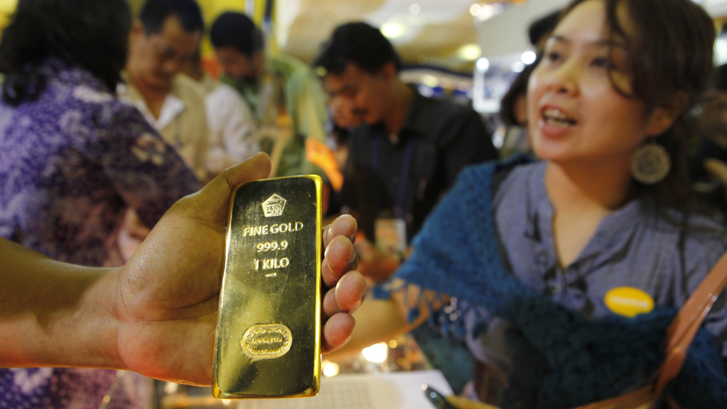 A man shows a gold bar to customers at a Jewellery Expo in Jakarta.