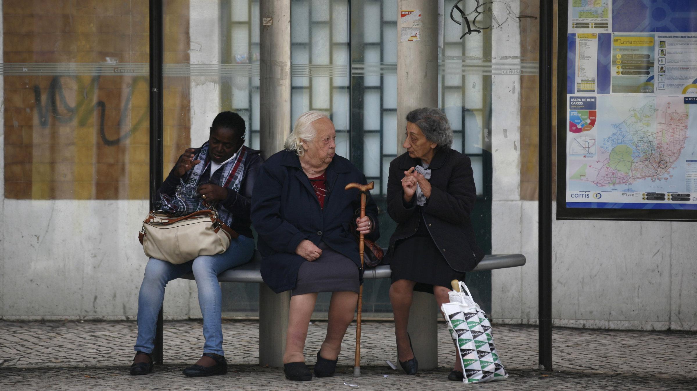 Women speak as they wait for a tram in Lisbon.
