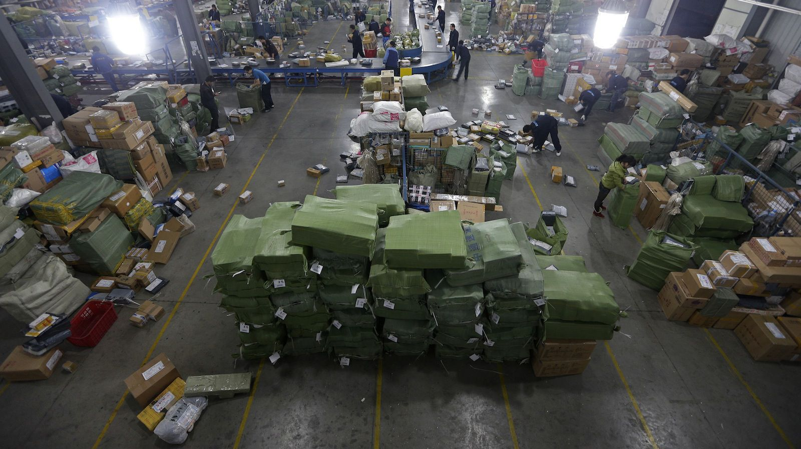 """A general view shows employees sorting packages along a conveyor belt at a hub of ZTO Express Delivery company in Wuhan, Hubei province November 12, 2012. According to China's delivery industry association, more than 800,000 employees of Chinese delivery companies were expected to be working for the """"Single's Day"""" online shopping promotion on Sunday led by Taobao.com, the country's biggest online purchase website. Alibaba, owner of Taobao, announced on Monday that the company cashed in 19.1 billion yuan (3.04 billion USD) during the promotion, Xinhua News Agency reported. Picture taken November 12, 2012. REUTERS/Stringer (CHINA - Tags: BUSINESS SOCIETY EMPLOYMENT) CHINA OUT. NO COMMERCIAL OR EDITORIAL SALES IN CHINA - RTR3AC1Y"""