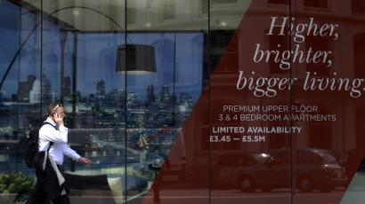 A man walks past the signage of a new property development advertising apartments for 5.5 million pounds sterling in central London.