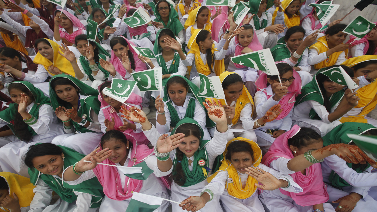 Female students wave Pakistan's national flag at a ceremony to celebrate the country's Independence Day at the mausoleum of Muhammad Ali Jinnah in Karachi