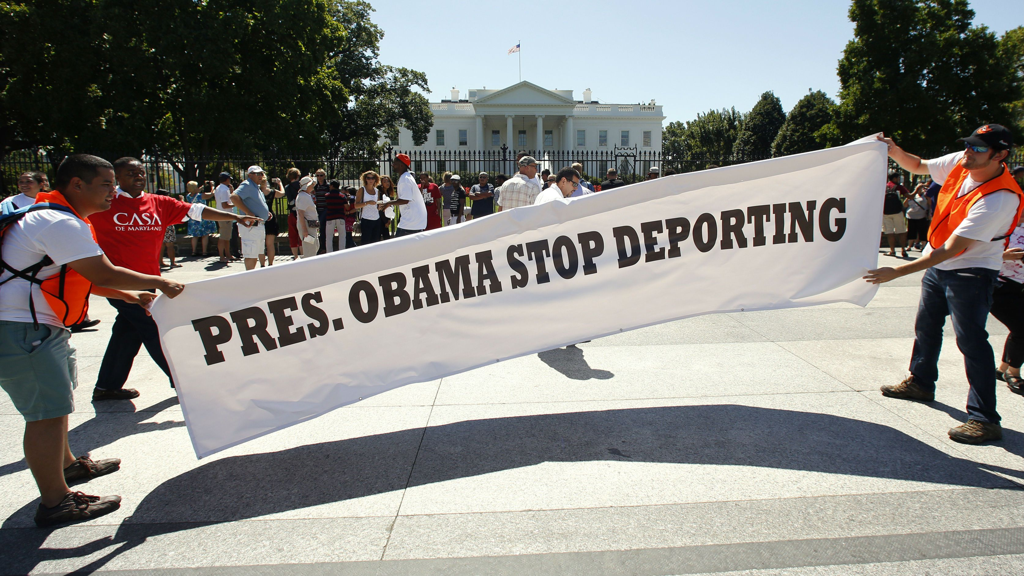 Anti-deportation protesters unfurl a sign in front of the White House in Washington August 28, 2014. The protest, organized by CASA, a non-profit organization helping immigrants, called on President Obama to stop deporting undocumented workers, parents and children.