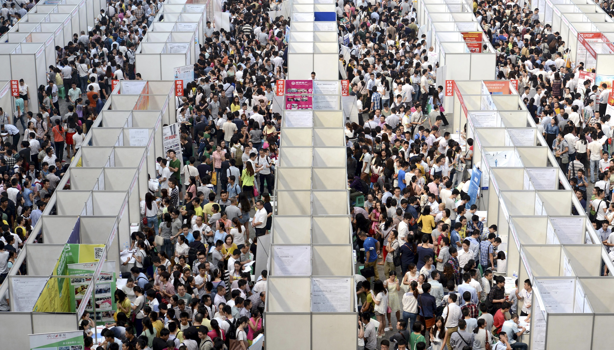 Thousands of job seekers visit booths at a job fair in Chongqing municipality, October 11, 2014. China's economy likely grew at its weakest pace in more than five years in the third quarter as a property downturn weighed on demand, a Reuters poll showed, raising the chances of more aggressive policy steps that may include cutting interest rates. The prospects of weaker growth may raise the chances of more aggressive policy steps such as cutting interest rates or reserve requirements across the board, but the government may not rush into action as the job market still appears to be holding up, analysts say. REUTERS/Stringer (CHINA - Tags: BUSINESS EMPLOYMENT POLITICS TPX IMAGES OF THE DAY) CHINA OUT. NO COMMERCIAL OR EDITORIAL SALES IN CHINA - RTR49RH7