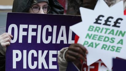 NHS workers hold placards during a strike, outside St Pancras Hospital in London October 13, 2014.