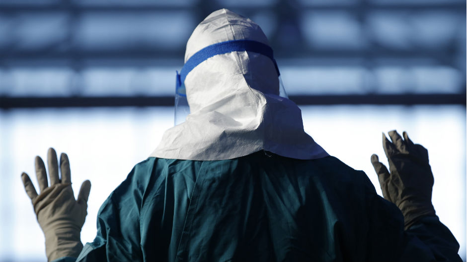 Barbara Smith, a registered nurse with Mount Sinai Medical Health Systems, St. Luke's and Roosevelt Hospitals in New York, demonstrates putting on personal protective equipment (PPE) during an Ebola educational session for healthcare workers at the Jacob Javits Convention center in New York, October 21, 2014.