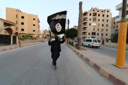 """A member loyal to the Islamic State in Iraq and the Levant (ISIL) waves an ISIL flag in Raqqa June 29, 2014. The offshoot of al Qaeda which has captured swathes of territory in Iraq and Syria has declared itself an Islamic """"Caliphate"""" and called on factions worldwide to pledge their allegiance, a statement posted on jihadist websites said on Sunday. The group, previously known as the Islamic State in Iraq and the Levant (ISIL), also known as ISIS, has renamed itself """"Islamic State"""" and proclaimed its leader Abu Bakr al-Baghadi as """"Caliph"""" - the head of the state, the statement said. REUTERS/Stringer (SYRIA - Tags: POLITICS CIVIL UNREST ) BEST QUALITY AVAILABLE - RTR4BHO3"""
