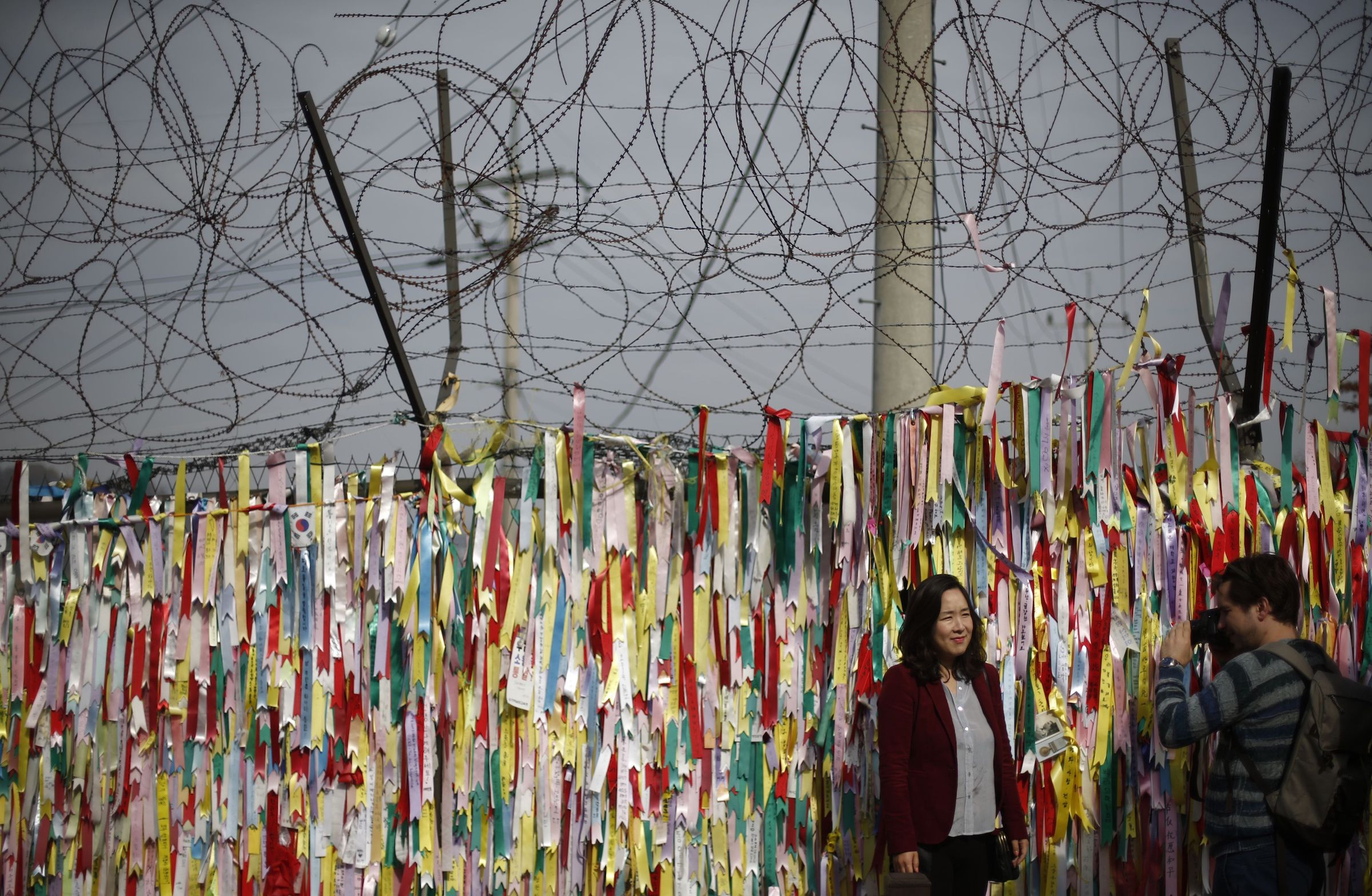 A barbed wire fence decorated with South Korean national flags is pictured near the demilitarized zone which separates North and South Korea in Paju October 31, 2014. On the 25th anniversary of the fall of the Berlin Wall, there are still barriers separating communities around the world, from the barbed wire fence dividing the two Koreas, the fence around the Spanish enclave of Melilla, to the sectarian Peace Wall in Belfast, the Israel-Gaza barrier and the border separating Mexico from the United States. Picture taken October 31, 2014. REUTERS/Kim Hong-Ji (SOUTH KOREA - Tags: ANNIVERSARY CIVIL UNREST POLITICS SOCIETY) ATTENTION EDITORS: PICTURE 19 OF 28 FOR WIDER IMAGE PACKAGE 'THE WALLS THAT DIVIDE' TO FIND ALL IMAGES SEARCH 'WALLS DIVIDE' - RTR4D2WC