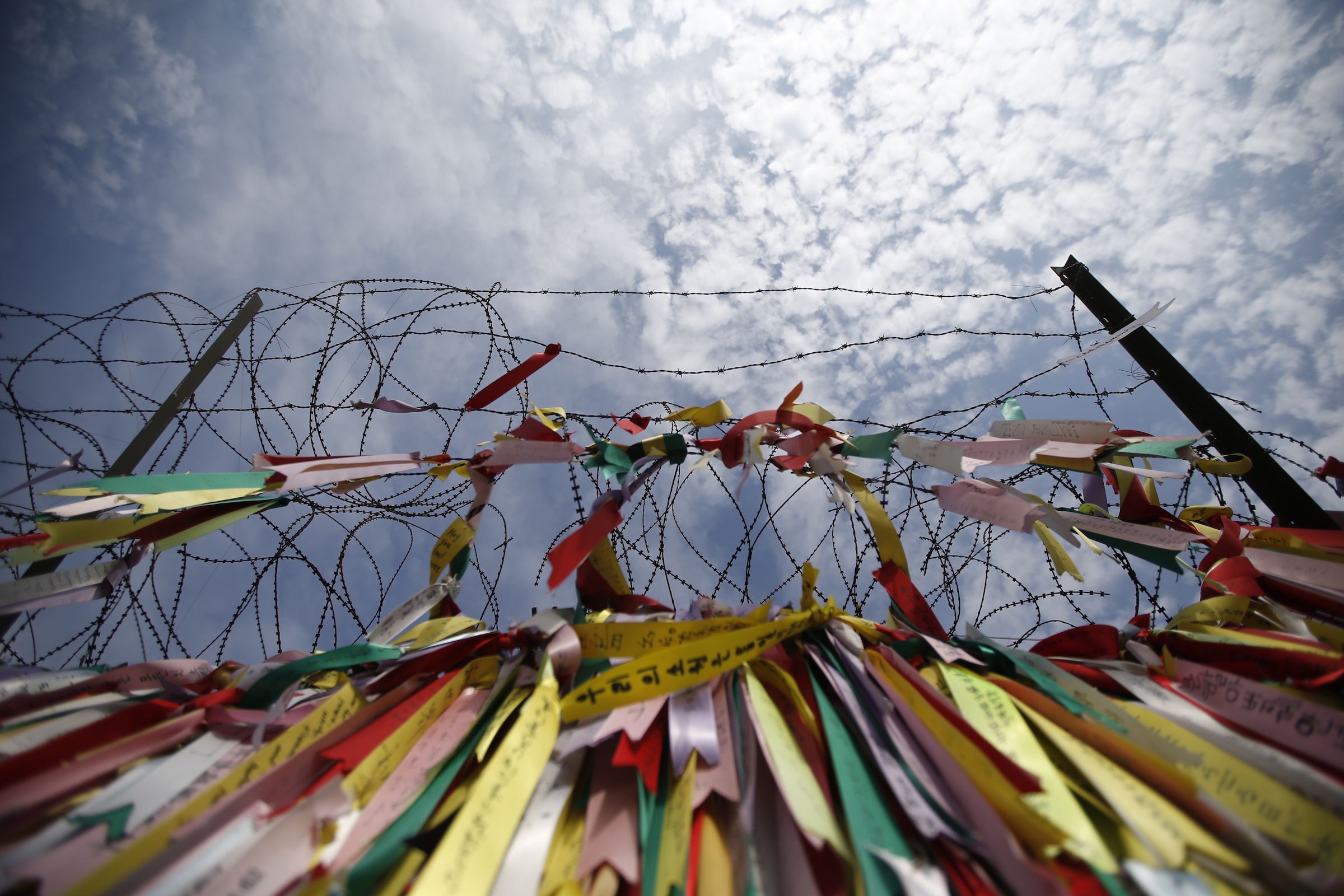 A barbed wire fence decorated with ribbons bearing messages wishing the unification of the two Koreas is pictured near the demilitarized zone which separates North and South Korea in Paju October 31, 2014. On the 25th anniversary of the fall of the Berlin Wall, there are still barriers separating communities around the world, from the barbed wire fence dividing the two Koreas, the fence around the Spanish enclave of Melilla, to the sectarian Peace Wall in Belfast, the Israel-Gaza barrier and the border separating Mexico from the United States. Picture taken October 31, 2014.  REUTERS/Kim Hong-Ji (SOUTH KOREA - Tags: ANNIVERSARY CIVIL UNREST POLITICS SOCIETY)  ATTENTION EDITORS: PICTURE 18 OF 28 FOR WIDER IMAGE PACKAGE 'THE WALLS THAT DIVIDE' TO FIND ALL IMAGES SEARCH 'WALLS DIVIDE' - RTR4D2WH