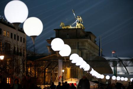 The installation 'Lichtgrenze' (Border of Light) along a former Berlin Wall location is illuminated next to the Brandenburg Gate, at dusk in Berlin November 7, 2014. A part of the inner city of Berlin is being temporarily divided from November 7 to 9, with a light installation featuring 8000 luminous white balloons, following the 9.5-mile (15.3 kmilometre) path the Berlin Wall once occupied, to commemorate the 25th anniversary of the fall of the Wall. REUTERS/Fabrizio Bensch (GERMANY - Tags: ANNIVERSARY ENTERTAINMENT) - RTR4DA9L