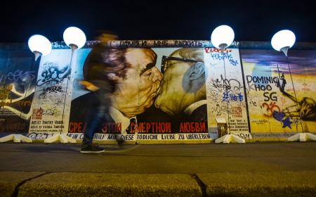 A person passes by the installation 'Lichtgrenze' (Border of Light) in front of a painting depicting former Soviet leader Leonid Brezhnev kissing his East German counterpart Erich Honecker (R) along the East Side Gallery, the largest remaining part of the former Berlin Wall, in Berlin November 7, 2014. A part of the inner city of Berlin is being temporarily divided from November 7 to 9, with a light installation featuring 8000 luminous white balloons, following the 9.5-mile (15.3 kmilometre) path the Berlin Wall once occupied, to commemorate the 25th anniversary of the fall of the Wall. REUTERS/Hannibal Hanschke (GERMANY - Tags: ANNIVERSARY ENTERTAINMENT CITYSCAPE TPX IMAGES OF THE DAY) - RTR4DAPP