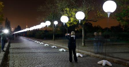 A person takes a photo of the installation 'Lichtgrenze' (Border of Light) along a former Berlin Wall location at Mauer Park in Berlin November 7, 2014. A part of the inner city of Berlin is being temporarily divided from November 7 to 9, with a light installation featuring 8000 luminous white balloons, following the 9.5-mile (15.3 kmilometre) path the Berlin Wall once occupied, to commemorate the 25th anniversary of the fall of the Wall. REUTERS/Pawel Kopczynski (GERMANY - Tags: ANNIVERSARY ENTERTAINMENT CITYSCAPE) - RTR4DAUN