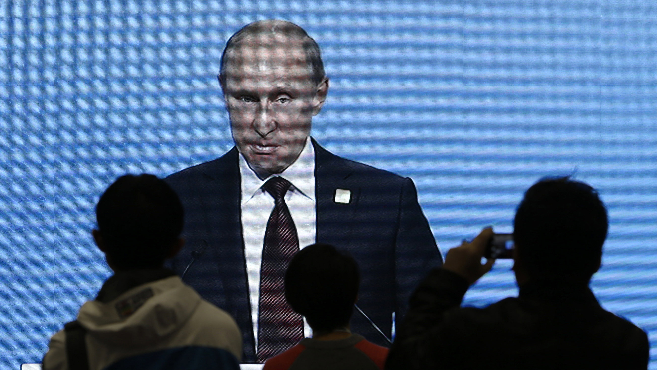 Journalists watch a live broadcast on an electronic screen showing Russia's President Vladimir Putin giving a speech during the APEC CEO Summit in Beijing, November 10, 2014.